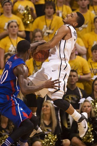 Missouri's Phil Pressey, right, has the ball held down by Kansas' Tyshawn Taylor, left, as he tries to shoot during the first half of an NCAA college basketball game on Saturday, Feb. 4, 2012, in Columbia, Mo. A jump ball was called on the play. (AP Photo/L.G. Patterson)