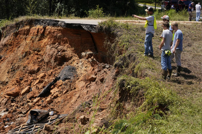 Mississippi Department of Transportation workers look at the deep hole on Mississippi Highway 26 in the Crossroads community, Tuesday, Aug. 31, 2021. Two people were killed and at least 10 others were injured when seven vehicles plunged, one after another, into the deep hole on the dark rural two-lane highway, which collapsed after Hurricane Ida blew through Mississippi. (AP Photo/Rogelio V. Solis)