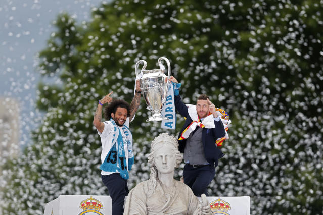 Real Madrid's captains Sergio Ramos and Marcelo, left, lift up the trophy next to the goddess Cibeles monument as the team arrives at the Cibeles square in Madrid, Spain, Sunday, May 27, 2018, after winning the Champions League final soccer match. (AP Photo/Francisco Seco)