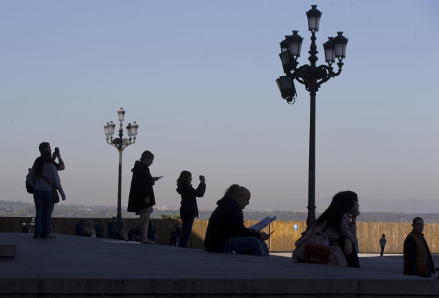 FILE - In this file photo dated Thursday, Oct. 25, 2018, tourists view the scene outside the Royal Palace in Madrid, Spain. Industry, Trade and Tourism Minister Reyes Maroto said Wednesday Jan. 16, 2019, that Spanish government figures show the country received a national record of 82.6 million foreign tourists last year. (AP Photo/Paul White, FILE)