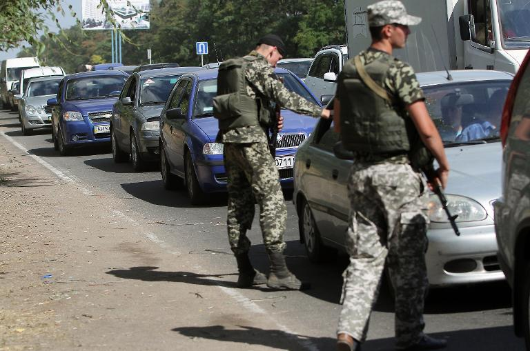 Ukrainian troops stop cars at a checkpoint as people flee the southeastern Ukrainian city of Mariupol in the Donetsk region amid fears of an offensive by pro-Russian militants on August 30, 2014