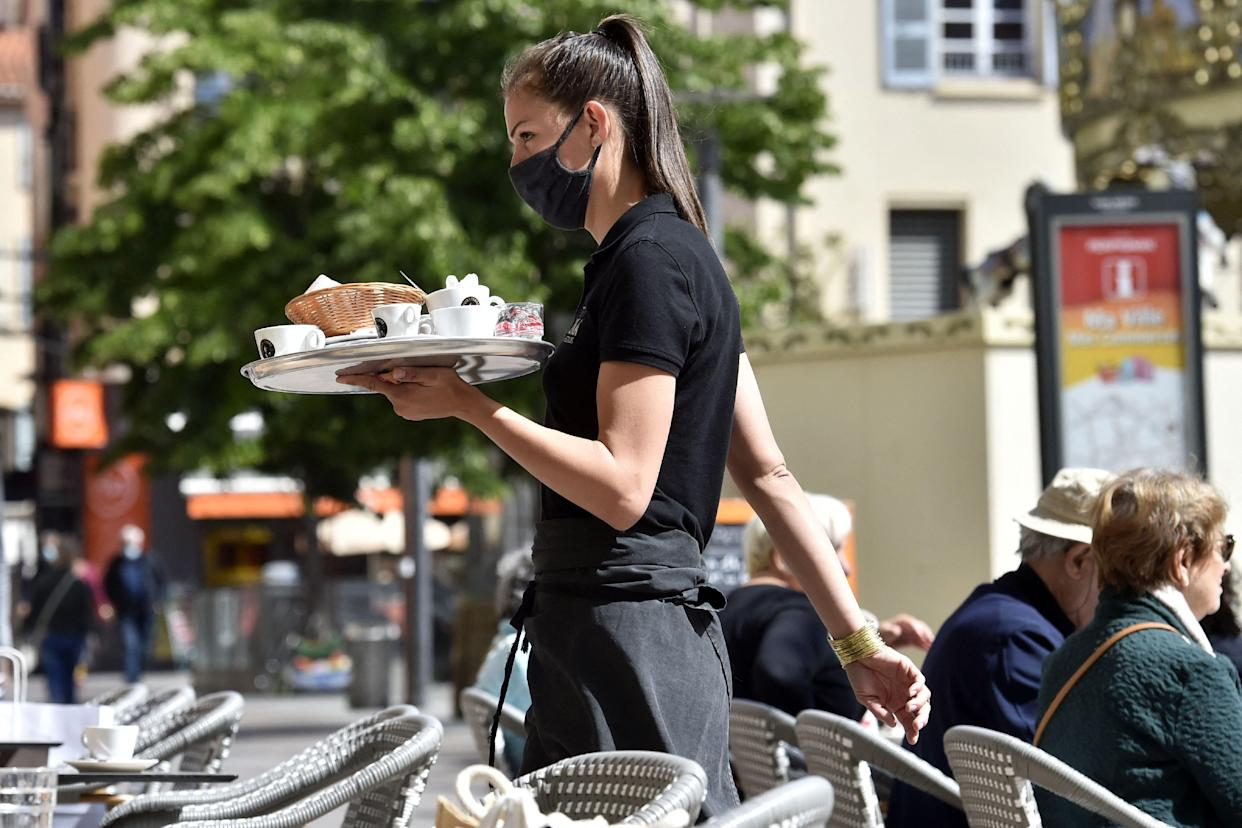 A waitress carries a tray as she walks past customers as they sit on a cafe terrace in Perpignan, south-western France on May 19, 2021, as cafes, restaurants and other businesses re-opened across France after closures during the coronavirus (Covid-19) pandemic. - Patrons have made their way back to cafes and prepared long-awaited visits to cinemas and museums as France loosened restrictions in a return to semi-normality after over six months of Covid-19 curbs. Cafes and restaurants with terraces or rooftop gardens can now offer outdoor dining, under the second phase of a lockdown-lifting plan that should culminate in a full reopening of the economy on June 30. (Photo by RAYMOND ROIG / AFP) (Photo by RAYMOND ROIG/AFP via Getty Images)
