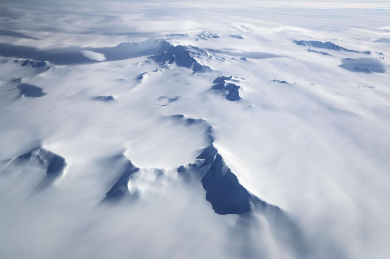<p>Mountains peek through land ice, as seen from NASA's Operation IceBridge research aircraft in the Antarctic Peninsula region on Nov. 4, 2017, above Antarctica. (Photo: Mario Tama/Getty Images) </p>