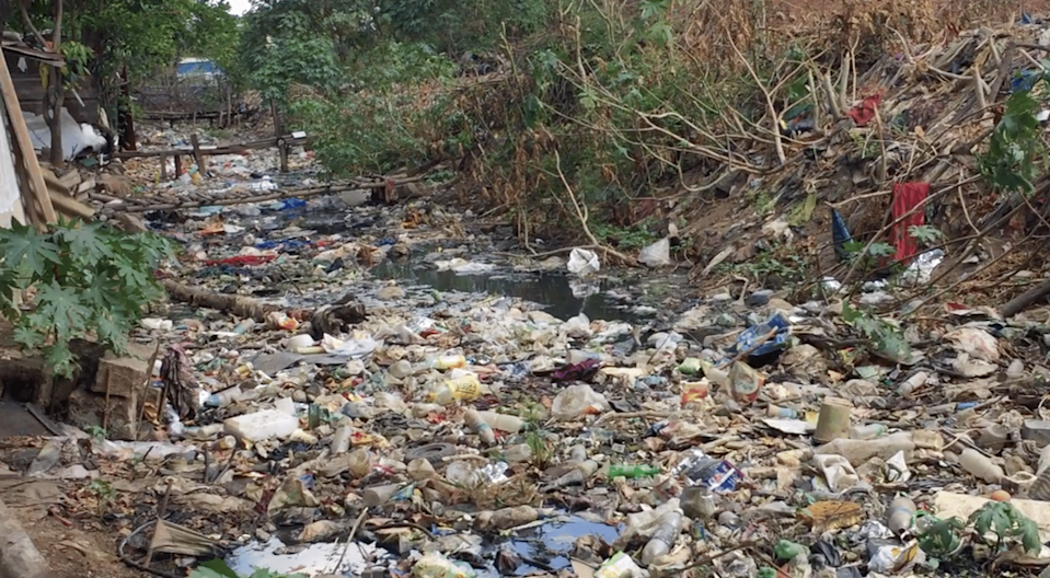 """<div class=""""paragraphs""""><p>A sewage stream, overflowing with garbage, flows adjacent to their homes.</p></div>"""