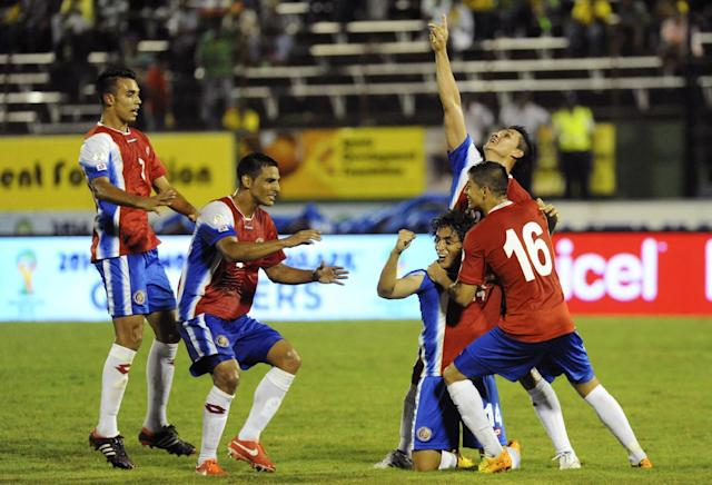 Costa Rica's Randall Brenes, kneeling at center, is congratulated by teammates after scoring against Jamaica during their 2014 World Cup qualifying soccer match in Kingston, Jamaica, Tuesday, Sept. 10, 2013. The game ended 1-1. (AP Photo/Collin Reid)
