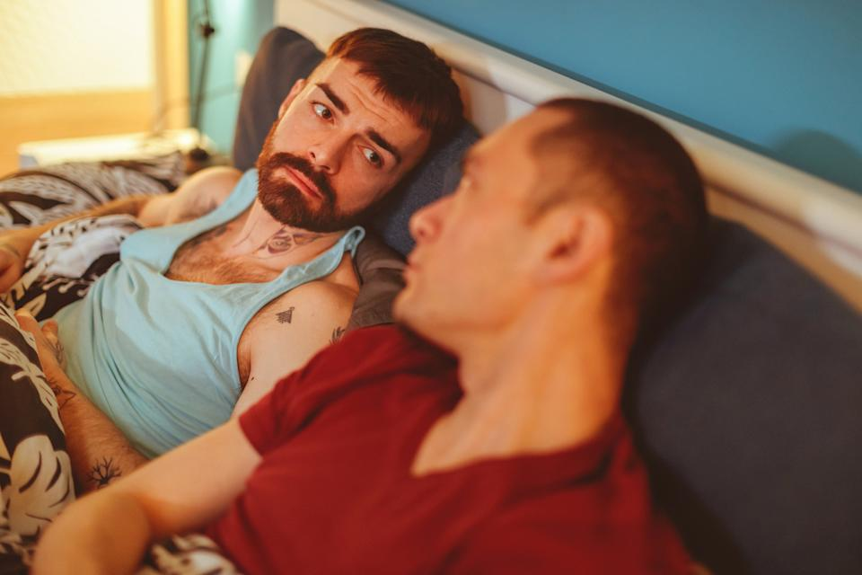 Sad man looking at his boyfriend lying in bed next to him