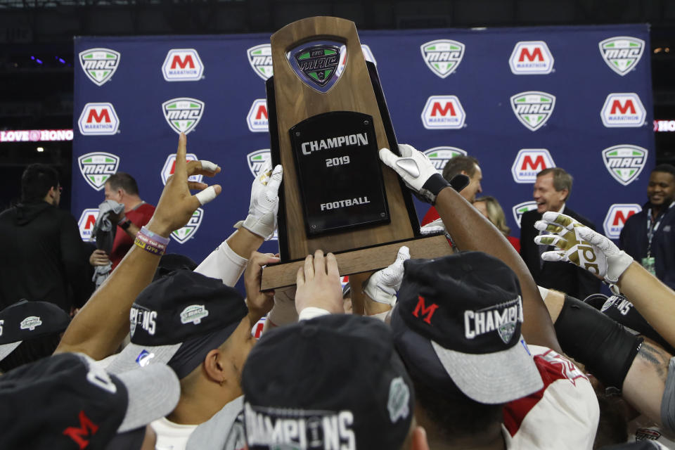 FILE - In this Dec. 7, 2019, file photo, members of the Miami of Ohio team hold the champion trophy after the Mid-American Conference championship NCAA college football game against Central Michigan, in Detroit. The Mid-American Conference on Saturday, Aug. 8, 2020, became the first league competing at college football's highest level to cancel its fall season because of COVID-19 concerns. With the MAC's 12 schools facing a significant financial burden by trying to maintain costly coronavirus protocols, the conference's university presidents made the decision to explore a spring season. (AP Photo/Carlos Osorio, File)