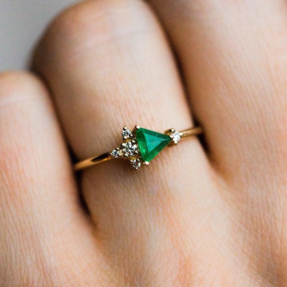 """<p>All eyes will be on the emerald in this <a href=""""https://www.popsugar.com/buy/14K-Yellow-Gold-Trillion-Emerald-Diamond-Cluster-Ring-532225?p_name=14K%20Yellow%20Gold%20Trillion%20Emerald%20With%20Diamond%20Cluster%20Ring&retailer=localeclectic.com&pid=532225&price=1%2C310&evar1=fab%3Aus&evar9=7954958&evar98=https%3A%2F%2Fwww.popsugar.com%2Fphoto-gallery%2F7954958%2Fimage%2F47021273%2F14K-Yellow-Gold-Trillion-Emerald-With-Diamond-Cluster-Ring&list1=shopping%2Cwedding%2Cjewelry%2Crings%2Cbride%2Cengagement%20rings%2Cfashion%20shopping&prop13=api&pdata=1"""" rel=""""nofollow noopener"""" class=""""link rapid-noclick-resp"""" target=""""_blank"""" data-ylk=""""slk:14K Yellow Gold Trillion Emerald With Diamond Cluster Ring"""">14K Yellow Gold Trillion Emerald With Diamond Cluster Ring</a> ($1,310).</p>"""