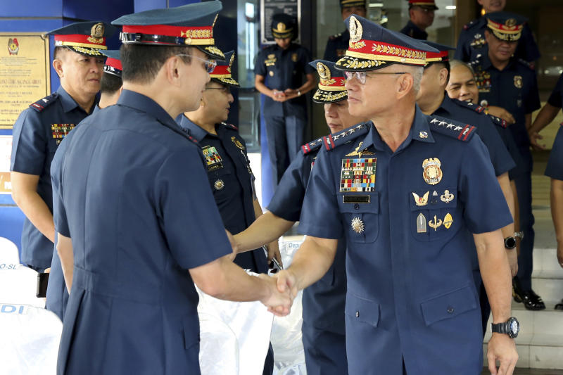 In this photo provided by Philippine National Police Public Information Office, Philippine National Police chief Gen. Oscar Albayalde, right, is congratulated by Police Maj.Gen. Guillermo Eleazar after the flag-raising ceremony at Camp Crame Monday, Oct. 14, 2019 in suburban Quezon city, northeast of Manila, Philippines. Albayalde resigned on Monday after he faced allegations in a Senate hearing that he intervened as a provincial police chief in 2013 to prevent his officers from being prosecuted for allegedly selling a huge quantity of illegal drugs they had seized. (Philippine National Police Via AP)