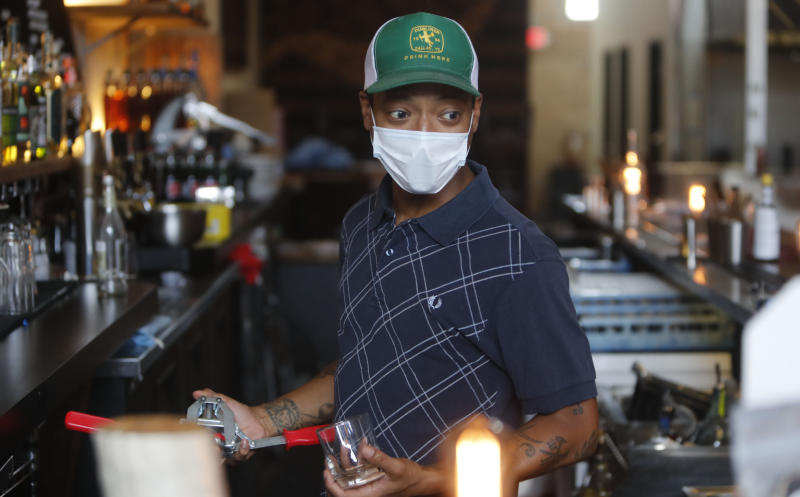 """Omar Yeefoon, owner of Shoals Sound & Service vegan restaurant works behind the bar while the eatery is closed Tuesday, June 30, 2020, in Dallas. Yeefoon reopened his Dallas restaurant June 10 to """"a pretty good reception,"""" after having been shuttered for three months. The comeback was fleeting. After four days, Yeefoon had to shut down again in the face of a COVID-19 resurgence in Texas and lay off two of the four workers he'd brought back. (AP Photo/LM Otero)"""