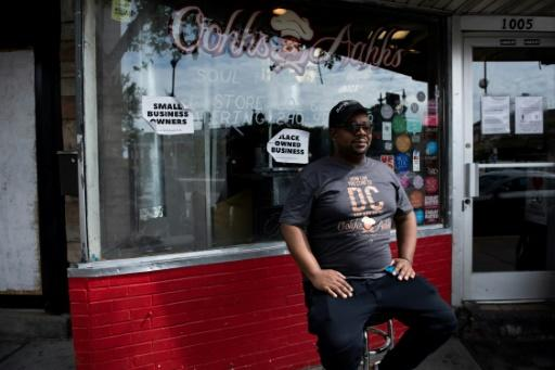 """Oji Abbott -- known as """"Chef O"""" -- sits in front of his restaurant Oohh's and Aahh's, on Washington's bustling U Street"""