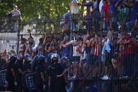 Mourning fans climb the fence of the presidential palace to get a glimpse of the casket carrying Diego Maradona's body in Buenos Aires, Argentina, Thursday, Nov. 26, 2020. The Argentine soccer great who was among the best players ever and who led his country to the 1986 World Cup title died from a heart attack at his home Wednesday at the age of 60. (AP Photo/Marcos Brindicci)