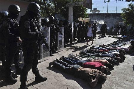 Inmates lie on the ground as riot policemen keep watch after a gunfight at the Tuxpan prison in Iguala