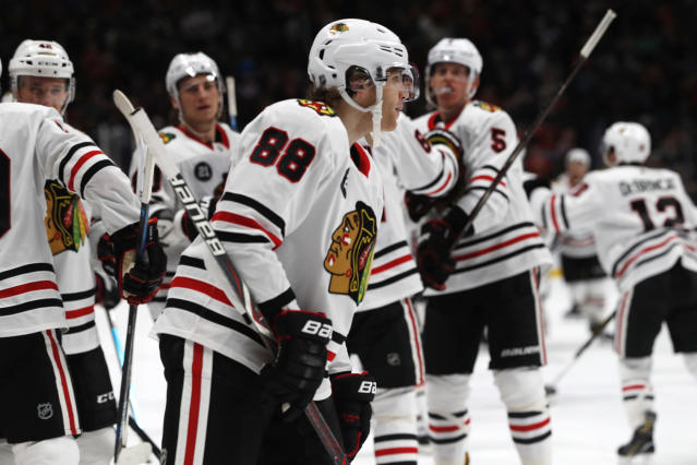 Teammates head to Chicago Blackhawks right wing Patrick Kane (88) after he scored against the Colorado Avalanche in overtime of an NHL hockey game Saturday, Dec. 29, 2018, in Denver. The Blackhawks won 3-2. (AP Photo/David Zalubowski)