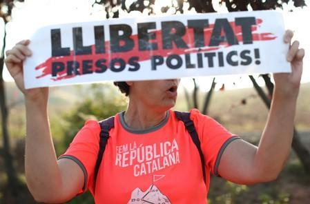 A woman holds a banner as she shouts slogans outside the Lledoners prison in Catalonia where jailed Catalan leaders await a verdict in a trial over a banned independence referendum in Sant Joan de Villatorrada