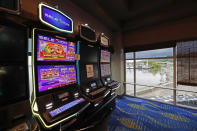 Two video slot machines await players while one in the middle sits out of service at the WaterView Casino and Hotel in Vicksburg, Miss., Thursday, May 21, 2020. Following a two-month shutdown due to coronavirus, casinos statewide are allowed to reopen Thursday, amid enhanced restrictions to keep customers and employees safe. (AP Photo/Rogelio V. Solis)