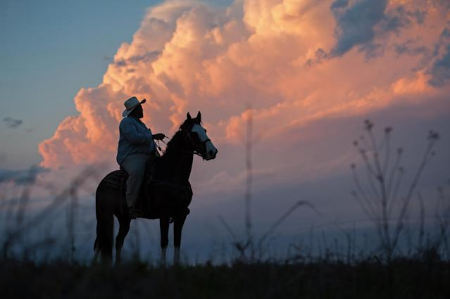 "<p>Cowboy ""Big Mike"" Jones watches a dramatic sunset in Isola, Miss., atop his favorite horse, Lucy, March 2018. (Photograph by Rory Doyle) </p>"