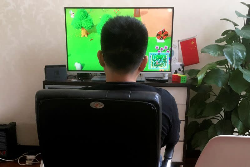 """Chinese tutor Zhao plays the game """"Animal Crossing"""" on Nintendo Switch at his apartment in Beijing"""