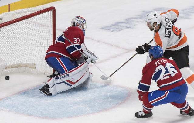 Philadelphia Flyers' Ivan Provorov (9) scores against Montreal Canadiens goaltender Keith Kinkaid as Canadiens' Jeff Petry defends during overtime NHL hockey action in Montreal, Saturday, Nov. 30, 2019. (Graham Hughes/The Canadian Press via AP)