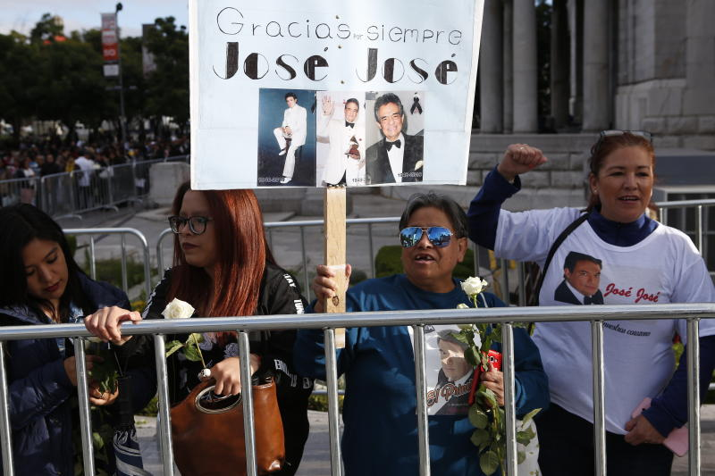 Fans waits outside the Palace of Fine Arts to say farewell to the ashes of Mexican singer Jose Jose, in Mexico City, Wednesday, Oct 9, 2019. Jose Jose died Sept. 28 in South Florida. His body was cremated in Miami, and it was agreed after a dispute among relatives over his remains, that half the ashes would remain there and the other half would be brought to Mexico. (AP Photo/Ginnette Riquelme)