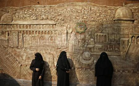Palestinian women stand in front of a mural depicting al-Aqsa mosque during a protest against the blockade on Gaza Strip, in Gaza City