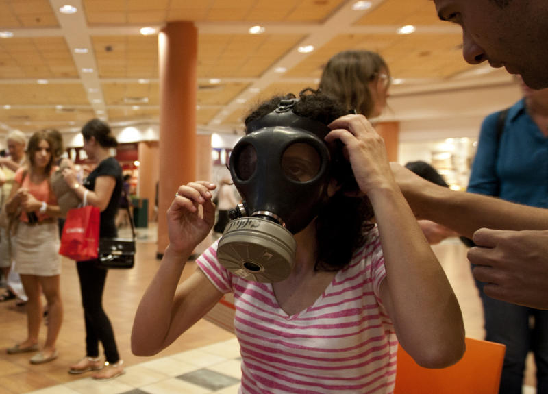 Israeli Hagit Ohana tries on a gas mask at a distribution center in a shopping mall in Mevaseret Zion near Jerusalem, Wednesday, July 25, 2012. Israel's foreign minister warned on Wednesday his country will act immediately if it discovers Islamic militants are raiding Syria's chemical or biological weapons stocks, while Israelis rushed to stock up on gas masks as the bellicose rhetoric swells. (AP Photo/Sebastian Scheiner)