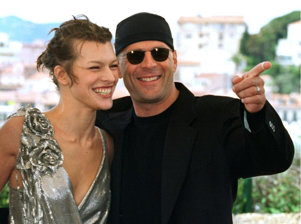 """US actor Bruce Willis (R) points alongside Ukrainian actress Milla Jovovich (L) during a photo call for French director Luc Besson's film """"Le Cinquieme Element"""", May 7. Besson's film, which is screened out of competition, opens the 50th Cannes Film Festival on the French Riviera."""