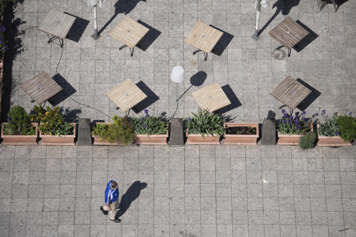 A man walks past the closed outdoor area of a restaurant in Frankfurt, Germany, Thursday, May 13, 2021. In Frankfurt, outdoor restaurants are not yet allowed to open. (Sebastian Gollnow/dpa via AP)