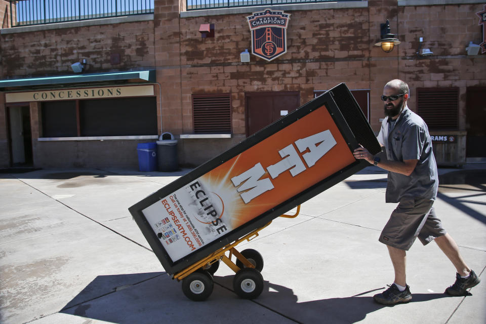 Mike Durkin, of Eclipse Cash Systems/Payment Alliance International, removes ATMs from Scottsdale Stadium, the spring training home of the San Francisco Giants, in Scottsdale, Ariz., Saturday, March 14, 2020. The remainder of spring training baseball games have been canceled due to the coronavirus outbreak. (AP Photo/Sue Ogrocki)