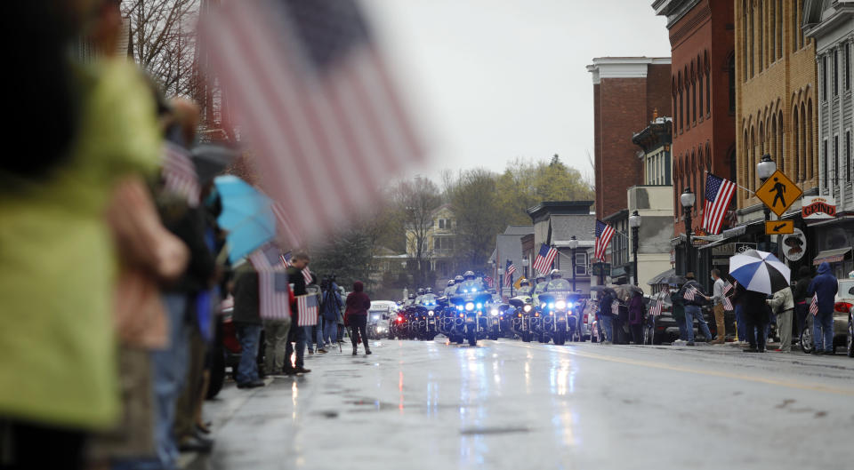 """Community members line the streets in downtown Adams, Mass., to pay their respects as the funeral procession for Capitol Police Officer William """"Billy"""" Evans leaves St. Stanislaus Kotska Church after his funeral, Thursday, April 15, 2021. Evans was killed this month when a driver struck him and another officer at a barricade outside the Senate. (Stephanie Zollshan/The Berkshire Eagle via AP)"""
