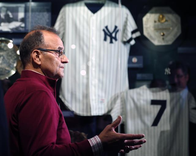 Former New York Yankees manager Joe Torre looks at a Yankees exhibit during his orientation visit at the Baseball Hall of Fame on Tuesday, March 25, 2014, in Cooperstown, N.Y. Torre will be inducted to the hall in July. (AP Photo/Mike Groll)