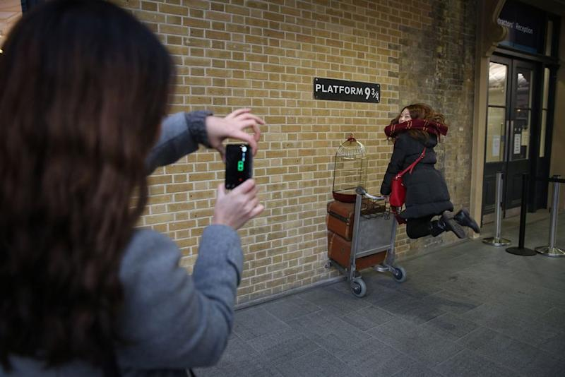 """London King's Cross station features a special area for """"Harry Potter"""" enthusiasts to take photos of themselves crossing the barrier at Platform 9 3/4. There is also a themed gift shop selling magical merch."""