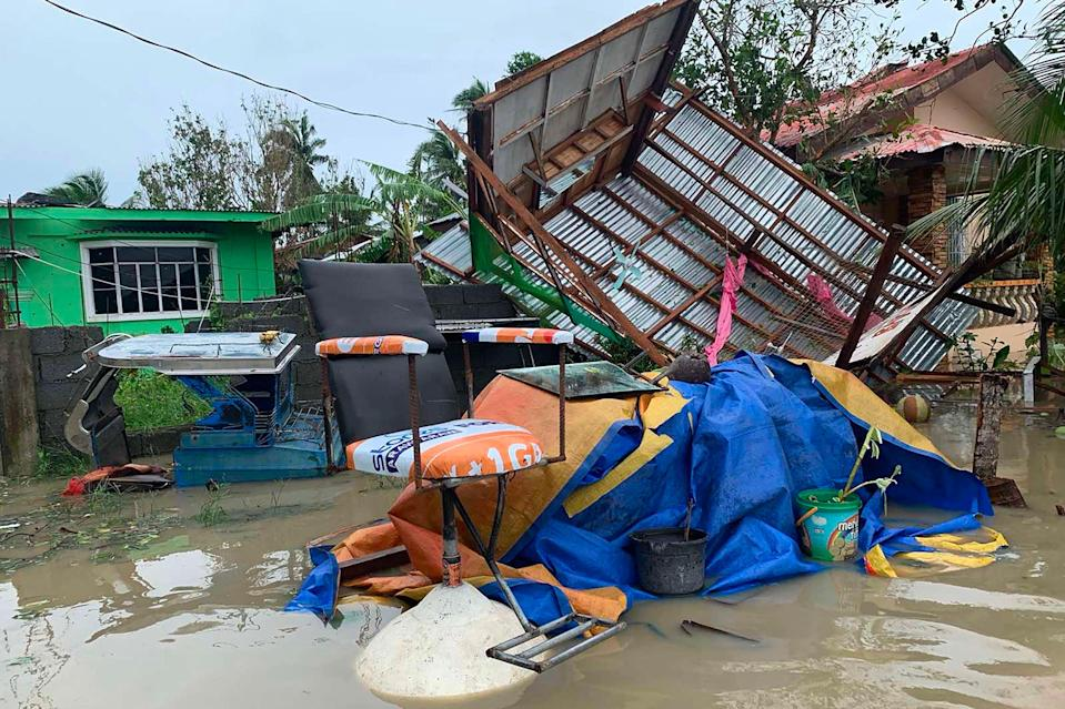 A destroyed house lies on its side after tropical storm Molave hit the town of Pola, Oriental Mindoro province (AFP via Getty Images)
