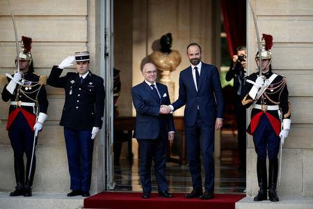 Newly-appointed French Prime Minister Edouard Philippe (R) is greeted by his predecessor Bernard Cazeneuve (L) during a handover ceremony at the Hotel Matignon, in Paris, France, May 15, 2017.    REUTERS/Benoit Tessier