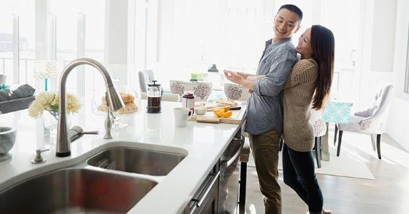 Couple embracing in the kitchen | Hero Images/Getty Images