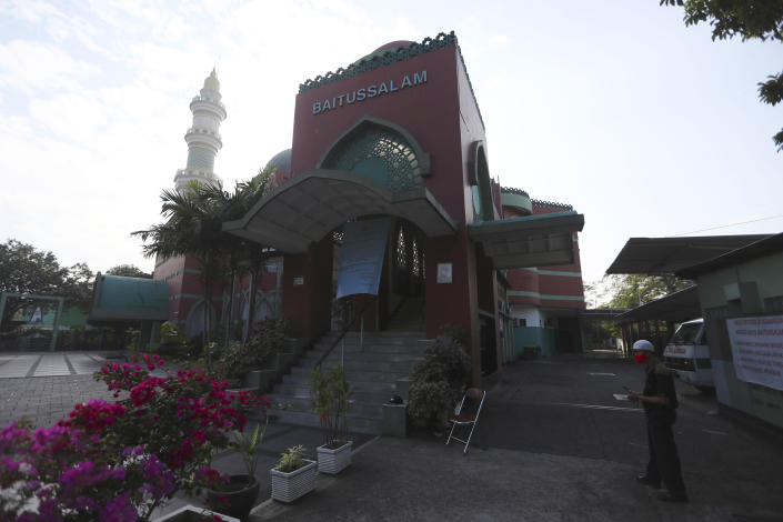 A man stands near an empty mosque in Jakarta, Indonesia, Tuesday, July, 20, 2021. Muslims across Indonesia marked a grim Eid al-Adha festival for a second year Tuesday as the country struggles to cope with a devastating new wave of coronavirus cases and the government has banned large gatherings and toughened travel restrictions. (AP Photo/Achmad Ibrahim)