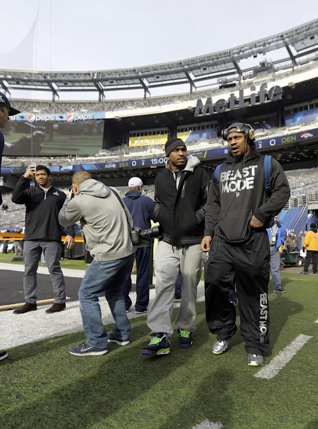 Seattle Seahawks quarterback Russell Wilson, left, and running back Marshawn Lynch, right, make a brief visit to MetLife Stadium along with other members of the team Saturday, Feb. 1, 2014, in East Rutherford, N.J. The Seahawks and the Denver Broncos are scheduled to play in the Super Bowl XLVIII football game Sunday, Feb. 2, 2014. (AP Photo/Jeff Roberson)