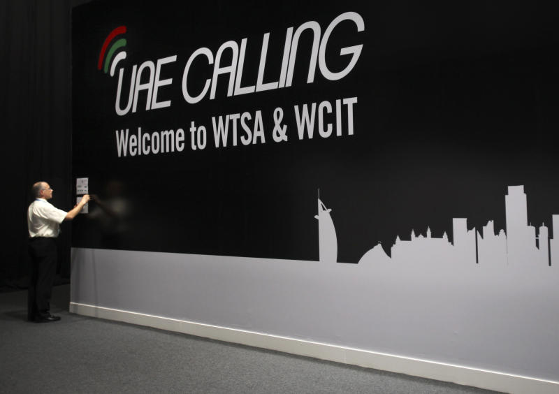 FILE-In this file photo dated Monday, Dec. 3, 2012, an official sticks a note on the wall next to the conference banner during the eleventh day of the World Conference on International Telecommunication in Dubai, United Arab Emirates. A U.N. conference weighing possible Internet rules shifted into high-stakes showdowns on Thursday after advancing a proposal for greater government oversight. The proposal was a blow to U.S.-led efforts to keep new regulations from touching the Net. (AP Photo/Kamran Jebreili, File)