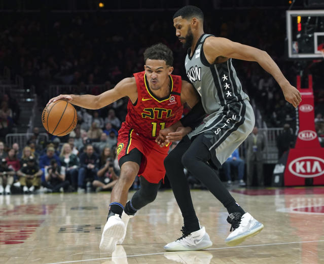 Brooklyn Nets guard Garrett Temple, right, defends against Atlanta Hawks Trae Young (11) in the second half of an NBA basketball game Friday, Feb. 28, 2020, in Atlanta. (AP Photo/Tami Chappell)