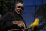 Valentin Faijoo looks at his caged birds sitting on a bench outside the San Jose Home for seniors where he lives in Tandil, Argentina, Wednesday, Sept. 15, 2021. Faijoo was allowed to take his pets to the residence during the COVID-19 pandemic lockdown and said it changed everything for good. (AP Photo/Natacha Pisarenko)