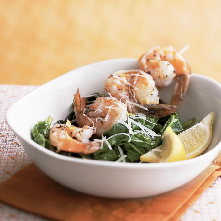 "<p>Parmesan cheese lends an intriguing flavor accent to garlic- and lemon-steamed shrimp in this recipe. And it's under 200 calories per serving. <a href=""http://www.eatingwell.com/recipe/264732/garlic-shrimp-on-spinach/"" rel=""nofollow noopener"" target=""_blank"" data-ylk=""slk:View recipe"" class=""link rapid-noclick-resp""> View recipe </a></p>"