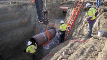 This April 13, 2020 photo provided by TC Energy shows workers for TC Energy installing a section of the Keystone XL crude oil pipeline at the U.S.-Canada border north of Glasgow, Mont. Two people working on the Keystone XL oil pipeline have tested positive for the coronavirus in northern Montana, but the company said Thursday, Aug. 8, 2020, that construction work on the disputed project will continue after a temporary shut down of a pipe storage yard. (TC Energy via AP)