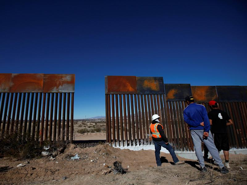 A worker chats with residents at a newly built section of the US-Mexico border fence: Jose Luis Gonzalez/Reuters