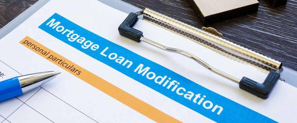 Mortgage loan modification application with pen and notepad.