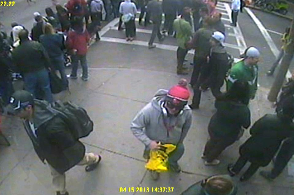 This frame grab from a video released by the FBI on Thursday, April 18, 2013, shows what the FBI are calling suspect number 1, in black cap, left, walking ahead of suspect number 2, towards top right in white cap, through the crowd in Boston on Monday, April 15, 2013, before the explosions at the Boston Marathon. (AP Photo/FBI)