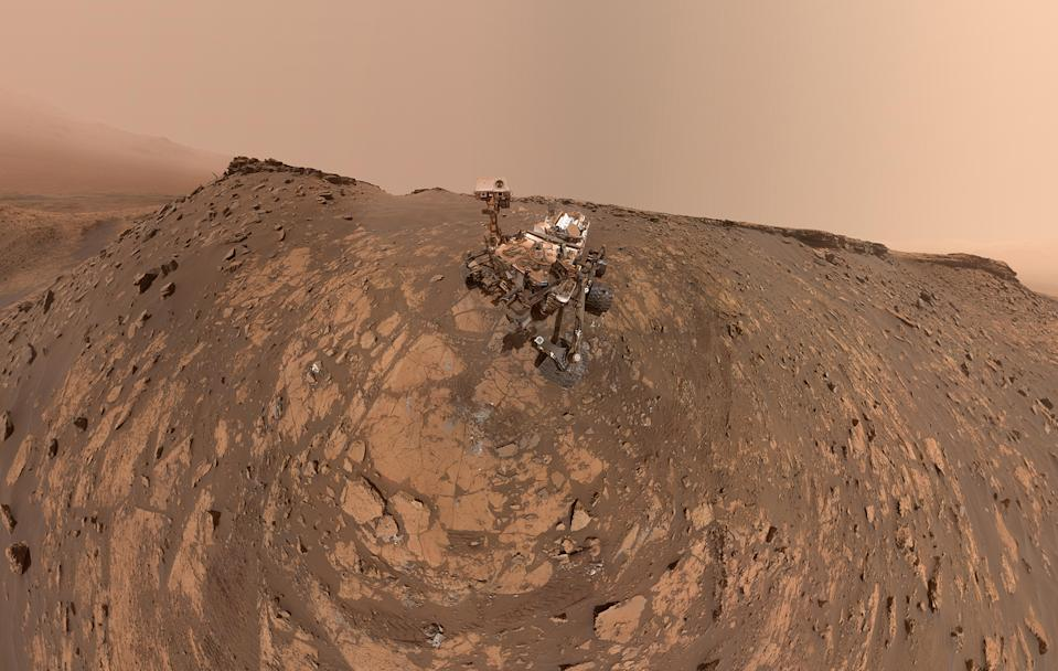 "NASA's Mars rover Curiosity snapped this selfie after drilling a hole at a rock feature called ""Hutton"" and making its way up to the Greenheugh Pediment, the rocky mound seen here behind the rover and to the left. This panorama combines 86 images taken by the Mars Hand Lens Imager (MAHLI) camera on Curiosity's robotic arm on Feb. 26, 2020, the 2,687th Martian day, or ""sol,"" of the rover's mission on the Red Planet."