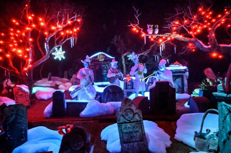 Inside the Haunted Mansion Holiday graveyard where ghost musicians play around graveyards, covered in fake snow