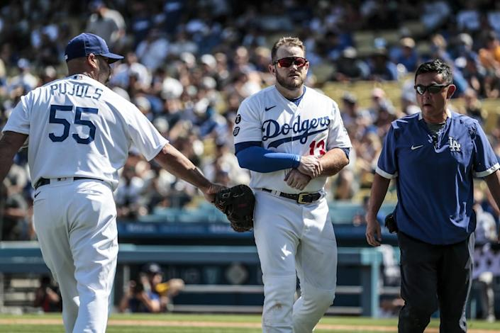 Dodgers first baseman Max Muncy leaves the field with a team trainer as Albert Pujols enters the game.