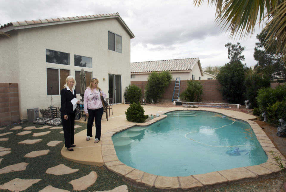 """Fafie Moore (L), a Reality Executives owner/broker, and realtor Helen Riley look over the backyard of a home being offered for sale in Henderson, Nevada April 8, 2013. Moore says private-equity firms and hedge funds have largely """"crowded out"""" local buyers since investment firms began buying homes here some eight months ago. Picture taken April 8, 2013. For use with Special Report VEGAS-HOUSING/   REUTERS/Steve Marcus (UNITED STATES - Tags: BUSINESS CONSTRUCTION REAL ESTATE)"""
