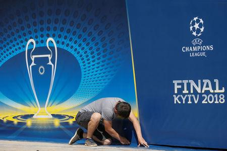 A man attaches a banner with the logo of the UEFA Champions League final in central Kiev, Ukraine May 23, 2018. REUTERS/Valentyn Ogirenko